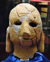 頬に線で「矢羽根」が刻まれている両面埴輪の一方の顔=和歌山市岩橋の和歌山県立紀伊風土記の丘で、八重樫裕一撮影