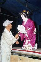 1990年の山谷の夏祭りで舞踊ショーを終え、駆け寄ってきた労働者と握手をする玉ちゃん=フォトジャーナリストの大島俊一さん撮影