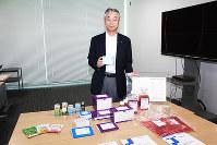 タカラバイオの製品を手にする仲尾功一社長。研究用試薬や細胞培養用培地・バッグ、健康食品などが並ぶ=滋賀県草津市の本社で、佐竹義浩撮影