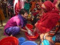 ベンガル語を駆使しながら、患部を清潔にする方法を指導する田中さん(2014年夏)=バングラデシュ北部タラゴンジ郡で、田中さん提供