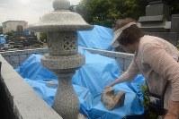熊本地震の被災者、中神さんは倒壊した墓に案内してくれた。お盆を過ぎても修復はかなわなかった=熊本県益城町で5月、宮崎稔樹撮影