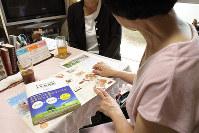 O朝刊はなれていてもエンディングノートなどを前に、死後のことをめいの敬子さんに話す和江さん(手前)=岡山市内で、反橋希美撮影