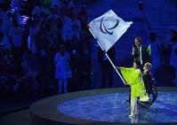リオデジャネイロのパエス市長(右奥)、IPCのクレーブン会長(同中央)から受け取ったパラリンピック旗を掲げる東京都の小池百合子知事=リオデジャネイロのマラカナン競技場で2016年9月18日、徳野仁子撮影
