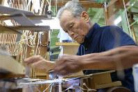 両手を素早く動かして帯を織る岩間利夫さん=京都市上京区の龍村美術織物烏丸工場で、小松雄介撮影