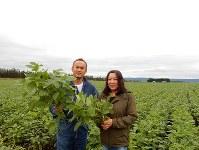 大豆を手にする折笠さん夫妻=小川節子撮影
