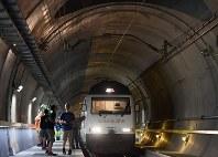 ゴッタルドベーストンネル内で停車した特別列車から降り、トンネル内を見学する乗客たち。運用開始までの間、避難などに使用する緊急時停車駅を歩いて回れる=スイス・エルストフェルト−ボディオ間で2016年8月25日、猪飼健史撮影