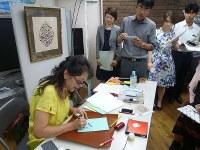 参加者の名前をアラビア書で書く佐川信子さん(左)=毎日メディアカフェで