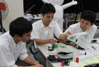 ビデオカメラをつけるヘッドバンドを調整する生徒ら。