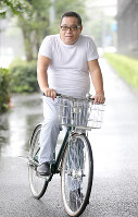 自転車にまたがる奥村隆記者=東京都千代田区で、宮武祐希撮影