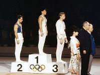 東京五輪体操男子つり輪で金メダルを獲得した早田卓次選手(表彰台中央)ら