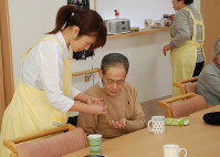 食後に服用する薬を受け取る認知症の男性(中央)=群馬県高崎市で、鳥井真平撮影