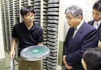 収集したフィルムを手に記録としての映像保存の必要性を語る松本さん(左)=福岡市早良区の市総合図書館で、三嶋祐一郎撮影