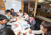 航海士(奥の2人)と航海体験を振り返る和歌山大生=「みらいへ」の船内で、山本芳博撮影