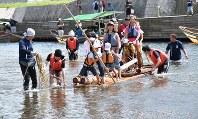 ゆらゆら揺れる筏に乗り、歓声を上げる家族連れ=亀岡市保津町の保津川で