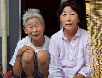 仮設住宅の縁側に並んで笑顔を浮かべる増永さん(左)と杉浦さん=熊本県益城町で、福岡賢正撮影