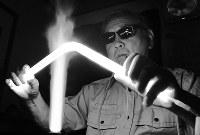 熱で軟らかくなったガラス管を折り曲げる沢田勝明さん。炎を当てるとガラス全体が輝きを放つ=大阪府吹田市のオプトガラス工業で、平川義之撮影