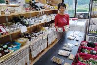 「かあちゃんの店」には、めはりずしなど紀州の味が並ぶ。商品を手にする竹田愛子さん=和歌山県新宮市熊野川町田長で、桜井由紀治撮影