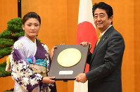 Japanese wrestler Kaori Icho, left, is presented with a plaque for her People's Honor Award by Prime Minister Shinzo Abe at the prime minister's office in Tokyo's Chiyoda Ward, on Oct. 20, 2016. (Mainichi)