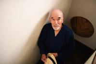 自宅階段で帽子を手に「これから散歩にでかけてきます」とポーズ。「『戦場の散歩』だから不思議な感じがするように撮ってよ」=東京都世田谷区で2016年10月5日、中村藍撮影
