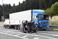 A car that rolled over after crashing into a large truck is seen along with the truck near the entrance of the Ouchi Junction on the Nihonkai-Tohoku Expressway in Yurihonjo, Akita Prefecture, on Oct. 21, 2016. (Mainichi)
