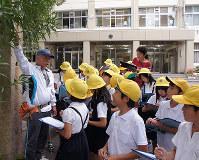 佐藤さん(左)の説明を熱心に聴き入る児童ら=滋賀県草津市立志津小で、衛藤達生撮影