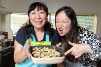 とろけるチーズをトッピングしたグラタンを手にポーズする枝元なほみさん(左)と西原理恵子さん=中村藍撮影