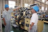 製作中の機械について従業員と話し合う小川孝史社長(左)=滋賀県長浜市の湖北精工本社で、佐竹義浩撮影