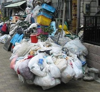 In this April 7, 2004 photo provided by Adachi Ward, trash is seen piled up in front of a home. This case became the spark for the creation of a 2013 ward ordinance to deal with so-called