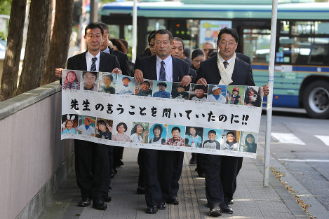 Bereaved family members of Okawa Elementary School students killed in the March 11, 2011 tsunami head to the Sendai District Court carrying a banner bearing photos of some of the victims, on Oct. 26, 2016. The banner reads,