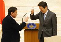 Philippine President Rodrigo Duterte, left, shares a toast with Japanese Prime Minister Shinzo Abe in Tokyo, on Oct. 26, 2016. (Mainichi)