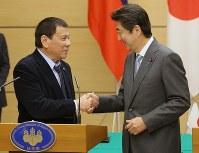 首脳会談で握手するフィリピンのドゥテルテ大統領(左)と安倍晋三首相=10月26日、宮武祐希撮影