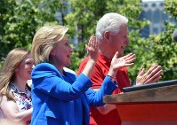 夫のビル・クリントン氏(右)、娘のチェルシーさん(左)とともに支持者らの声援に応えるヒラリー・クリントン氏(中央)=2015年6月13日、西田進一郎撮影