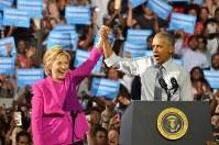 ヒラリー・クリントン氏の手を高々と掲げ応援するバラク・オバマ大統領=シャーロットで2016年7月5日、西田進一郎撮影