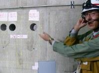 コンクリート壁からサンプル用コアの抜き取り状況を説明する中部電職員=御前崎市の浜岡原発で