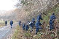 現場近くの雑木林で遺留品を捜索する捜査員=函館市で