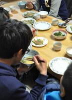 ボランティア(左)と食卓を囲む子どもたち=和歌山市楠見中で、成田有佳撮影