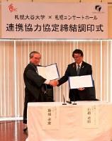 調印式で握手する巌城学長(左)と山越支配人