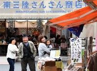 南三陸さんさん商店街で談笑する来訪者ら。奥のフードコートはこの日も満席だった=宮城県南三陸町で2016年11月20日、丸山博撮影