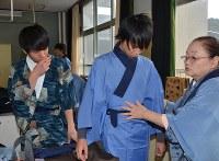 着物教室の講師(右端)から着付けを学ぶ東舞鶴高の男子生徒=京都府舞鶴市泉源寺の同校で、鈴木健太郎撮影