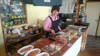 「まちなかキッチン」で働く古畑普さん。テーブルには約15種類の総菜が並び、店内でも食べられる=和歌山県白浜町で、桜井由紀治撮影