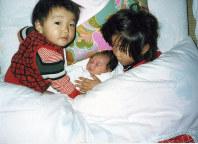 2歳 生まれたばかりの妹佐知子さんを囲んで