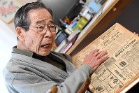 Yasuhiko Nishimura speaks of his war experience as he holds the archived article of the Osaka Mainichi Shimbun published on Dec. 8, 1941, the day of the Pearl Harbor attack. (Mainichi)