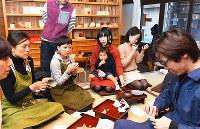 金継ぎワークショップで、参加者の子どもを抱きながら輪に加わる矢島里佳さん(中央)=京都市下京区で、川平愛撮影