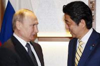 遅れてやって来たプーチン氏(左)を歓待する安倍首相=AP