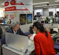 品川成年後見センターで社協職員と情報交換する市民後見人の横地明宏さん(左)=有田浩子撮影
