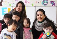 保育部の幼児たちと。卒業生のカミムラ・マリアナさん(右)と先週卒業したばかりのマシャド勇気さん=滋賀県東近江市甲津畑町で、大澤重人撮影