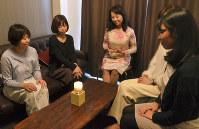 キャンドルセラピーの炎を見つめてくつろぐ参加者たち=東京都港区で、上東麻子撮影