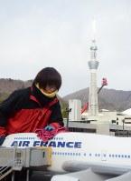 ミニチュアの飛行機の汚れを拭き取る職員。後方には東京スカイツリーも=日光市の東武ワールドスクウェアで