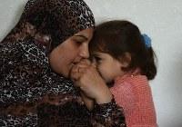 娘のハヤト・ジアードちゃん(3)をあやすハナディ・ナデムさん(31)。病気の夫に代わり8人きょうだいの長男(13)が働くが家賃が払えずアパートを追い出された。都市部では長引く避難に生活が困窮している家庭が少なくない=ヨルダン・アンマンで2016年9月23日、久保玲撮影