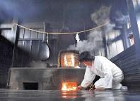 「鳴釜神事」のために火をおこす。竃の下には鬼の首が埋められたと伝えられ、釜の鳴動で吉凶を占う=岡山市北区の吉備津神社で、小関勉撮影